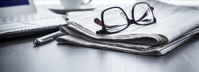 Pair of glasses resting on a newspaper