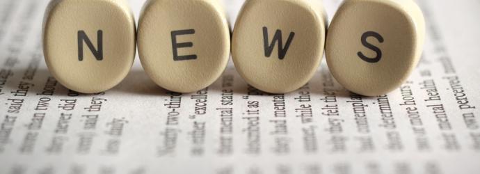 scrabble type letters spelling out NEWS on a book