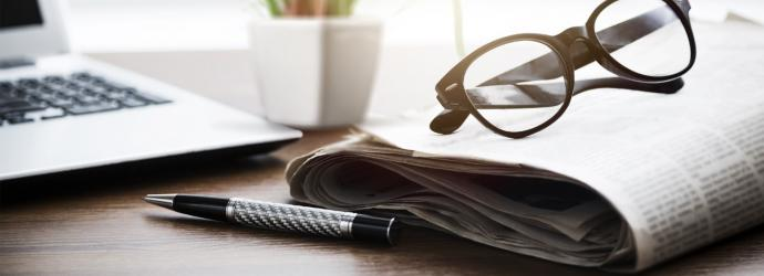 stylised image of a pair of glasses sitting on top of a folded newspaper