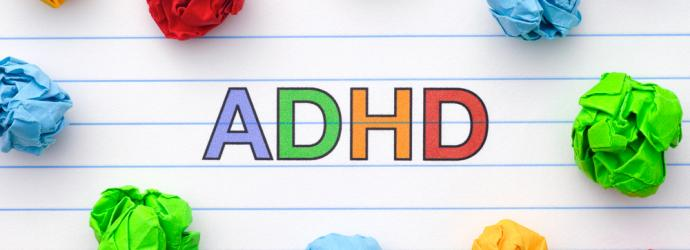 ADHD written on a piece of paper with scrunched up colourful paper around it