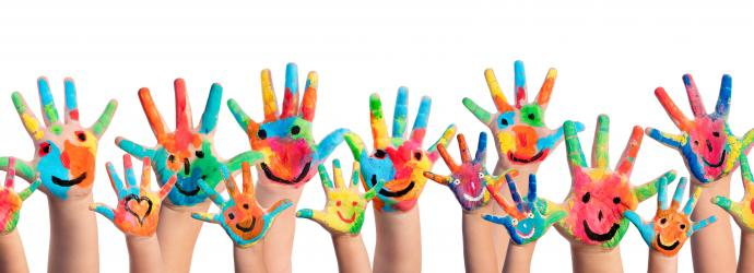 Children's hands waving with colourful smiley faces painted on them