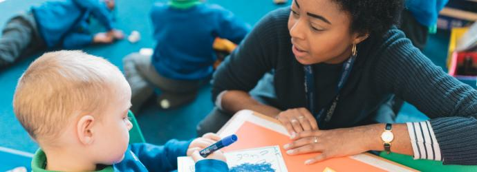 Image shows a teacher talking to a primary aged pupil who is colouring in.