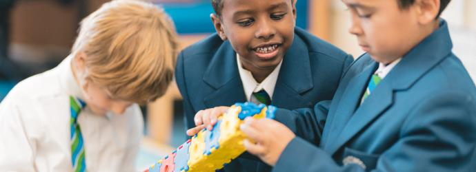 Image shows three primary aged schoolchildren building a Lego tower