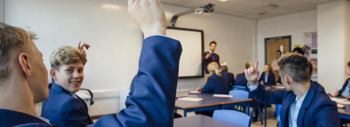 Male teacher in a secondary classroom teaching