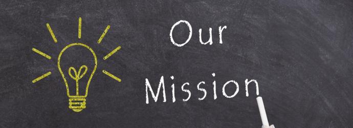 Our mission written on a chalkboard in white alongside a yellow light bulb also written on the chalk board