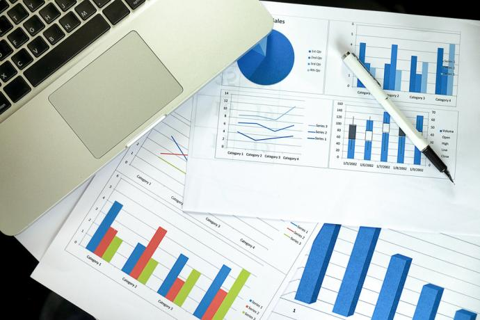 Paperwork with charts and graphs on a table with a laptop