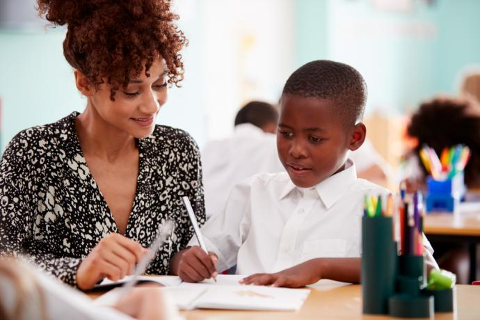 Female teacher providing teaching support for young male pupil - primary