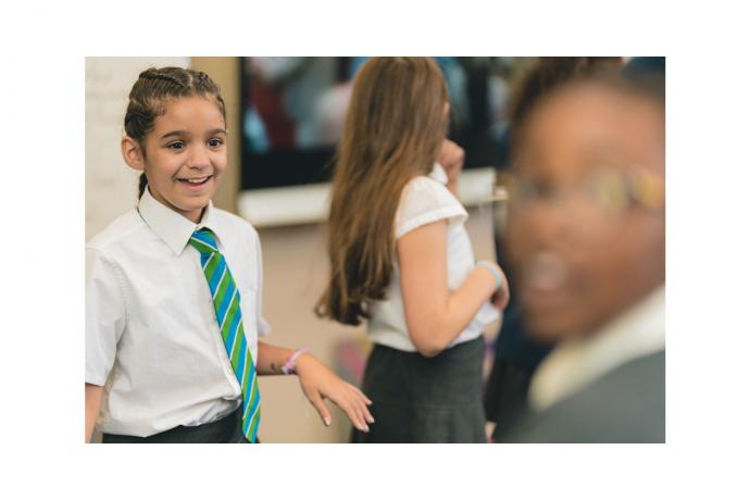 Image shows primary aged pupils walking around their classroom and laughing.