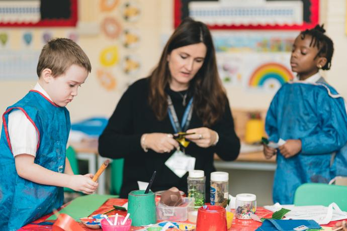 Image shows teacher helping two primary-aged children cut up coloured paper to make musical instruments