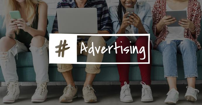 """group of people sat down with a box stating """"# Advertising"""""""
