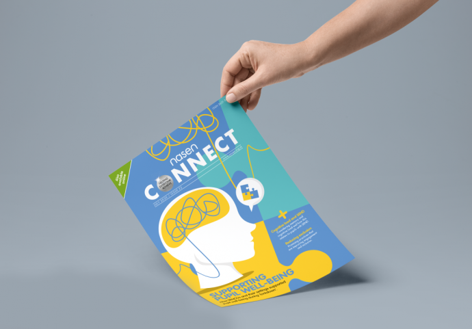 Person holding the july edition of nasen Connect on a grey background. Cover image shows a outline of a face with a yellow mark out for the brain which is connected with blue string.