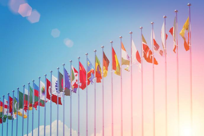 Image of flag poles with multiple countries flags with a bright blue sky in the background