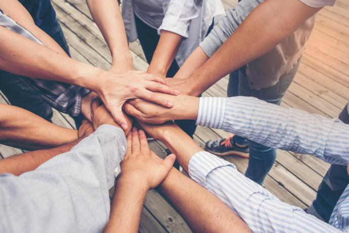 Group of people with their hands out in the middle of a circle