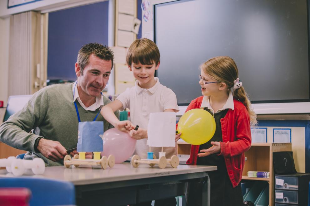 Male teacher supporting two primary school children in a lesson